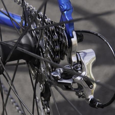 Closeup of rear cassette of road bike including rear derailleur taken through the spokes of the rear wheel