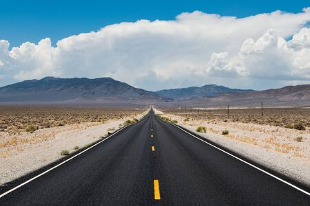 Long highway through a barren desert landscape to mountains under a sky with dramatic storm clouds in western Nevada Foto de archivo