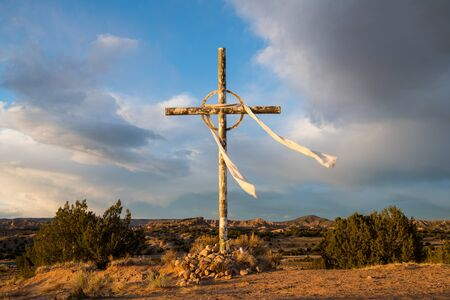 Cross under dramatic sky and clouds in the high desert landscape on the pilgrimage route from Santa Fe, New Mexico to the Sanctuario de Chimayo Stockfoto