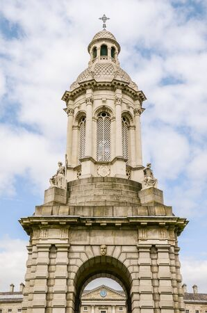 Ornate bell tower under blue sky and fluffy white clouds - The Trinity College Campanile in Dublin, Ireland with the Regent House roof and clock centered in the arch of the tower