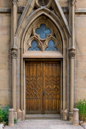 Rustic ornate wood door in a Gothic architecture facade of an old church - Loretto Chapel in Santa Fe, New Mexico