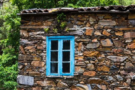 Close up of a window with blue trim and a rustic stone wall in the village of Cerdeira, Portugal