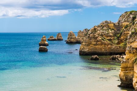 Seascape of calm blue water and high cliffs and rock formations at the Praia da Dona Ana beach in Lagos on the Algarve coast of Portugal