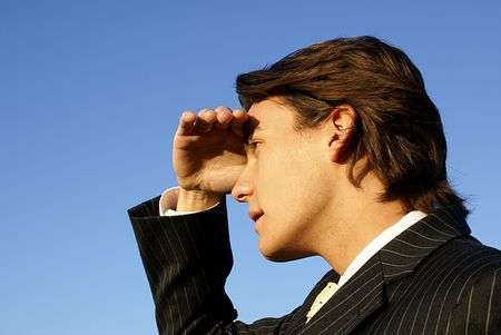 Man shielding his eyes looking into the horizon Stock Photo
