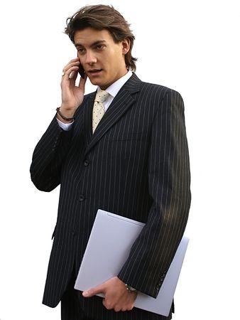 Businessman holding a notebook and talking on a cellphone Standard-Bild