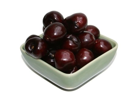 A bowl of cherries over white