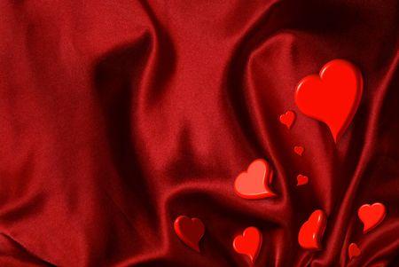Valentine hearts sprinkled on a red satin background