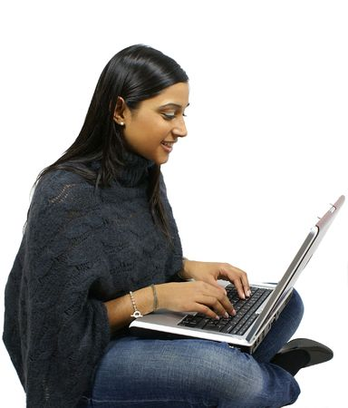 Asian Girl sits cross legged with a laptop