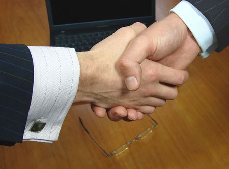Focus on handshake over a table with glasses and laptop in the background