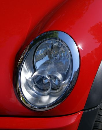 Headlight on a small red car in close up