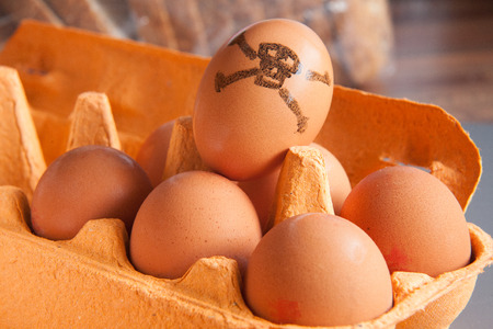 Tray of brown eggs, one marked with a skull & crossbones