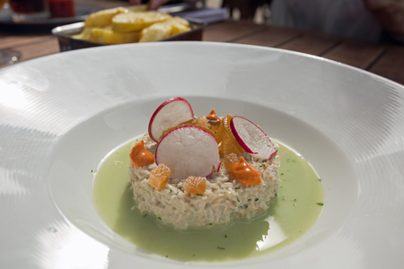 Delicious crab salad in watercress sauce topped with pears, radish and paprika Stock Photo