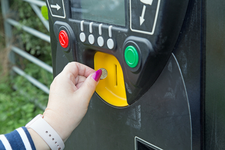 A female hand reaches to put a coin in the slot of a parking ticket dispensing machine