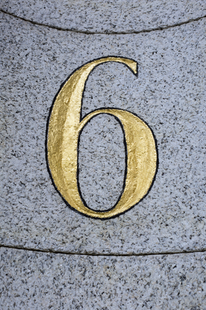Gilded number 6 chased into stone