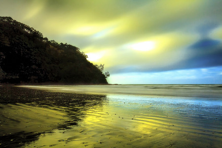 wind blowing: Long exposure seascape over fast moving clouds with wind blowing water and sand