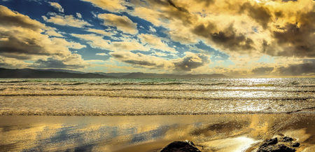 Tranquil isolated beach with lazy waves and puffy clouds Stock Photo