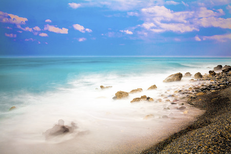 Long exposure rocky beach seascape with puffy clouds