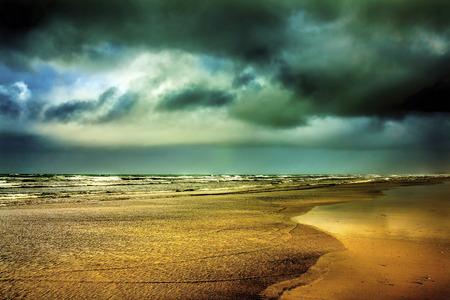 oceanscape: Powerful clouds over serene seaside beach seascape