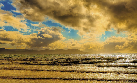 puffy: Colorful puffy clouds and lazy waves over pristine remote beach Stock Photo