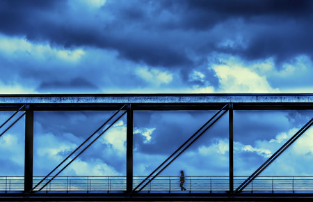 Sky bridge with person walking with puffy clouds in background