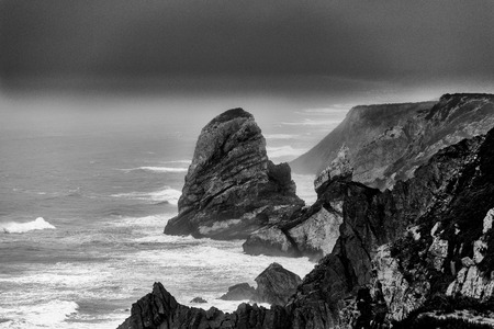 oceanscape: Foggy stormy ocean with rocks formations in background