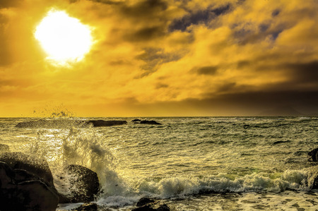 Beautiful sunset seascape with choppy seas and rock formations in background