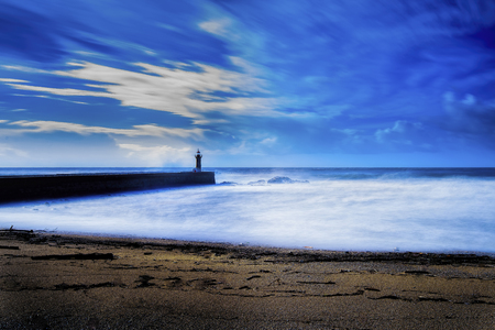 Lighthouse long exposure seascape with milky waves Stock Photo