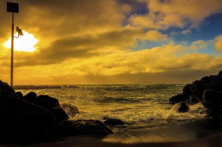 Waves pounding a rocky beach sunset seascape
