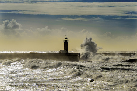 huge: Lighthouse deluged by huge waves Stock Photo