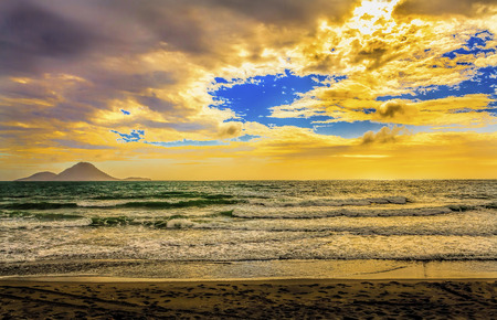 Happy volcano with sandy beach and choppy seas