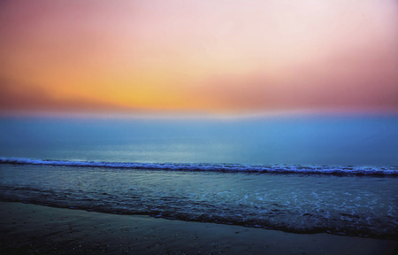 oceanscape: Foggy sunrise seascape with colorful skies and lazy waves