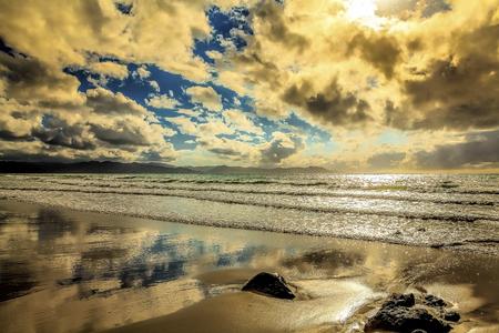 Majestic Kiwi beach with puffy clouds Stock Photo