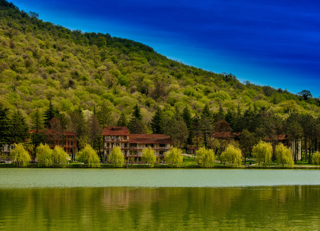 Tranquil lake vista with houses, mountain and blue skies