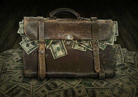 Antique briefcase filled and overflowing with money, fifty and one hundred dollar bills.