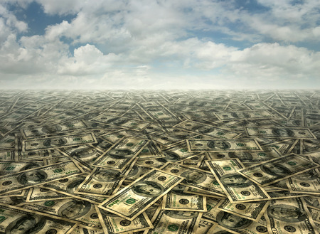 fifty dollar bill: Background of fifty and one hundred dollar bills underneath a cloudy sky. Stock Photo