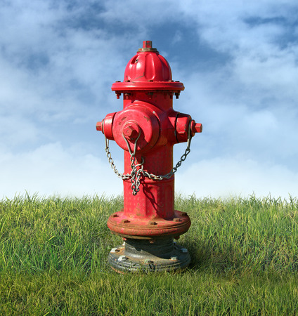 Red fire hydrant in a lawn of green grass and isolated against a blue sky. Stock Photo