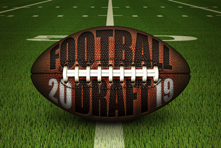 Illustration of a football with FOOTBALL DRAFT and 2019 embossed onto it; stting on the 50 yard line. 3D Illustration Stock Photo
