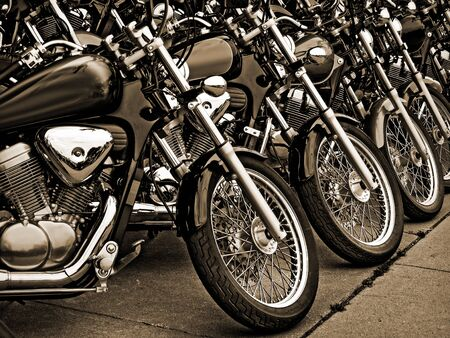 Sepia tone photograph of similar style motorcycles parked side by side. Archivio Fotografico