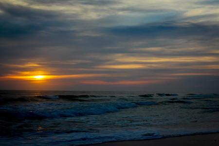 Beautiful and dramatic sunset beach scene of the Emerald Coast of Florida with waves slowly washing ashore.
