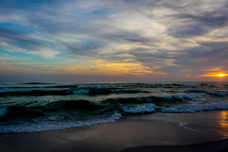 Beautiful and dramatic sunset beach scene of the Emerald Coast of Florida with waves slowly washing ashore. Sky is deep blue, red, crimson, orange, yellow, the water a beautiful dark teal, and the sand is a sugary white all in the Florida panhandle. The end to a beautiful day.