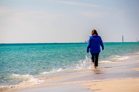 Beautiful beach scene of the Emerald Coast of Florida with people and/or dog, Waves slowly washing ashore. Sky is deep blue, water a beautiful teal, and the sand is a sugary white all in the Florida panhandle.