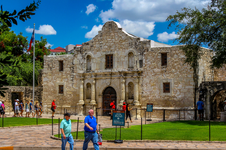 Exterior view of the historic Alamo in San Antonio, Texas and the surrounding area. With tourists with a bright blue sky and white fluffy clouds
