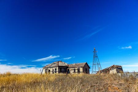 Granja abandonada de la era del tazón de polvo en la región del Panhandle de Texas. La casa y los edificios agrícolas circundantes han estado abandonados durante décadas. Los implementos agrícolas oxidados e inactivos como cultivadores, sembradoras y arados se sientan en el campo cercano y se oxidan.