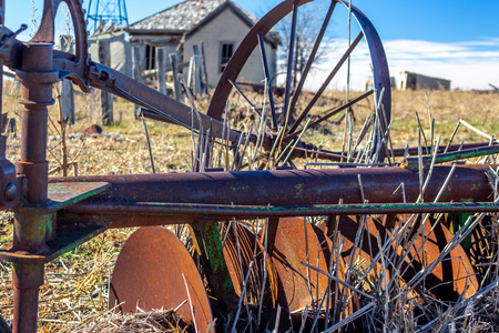 Dust bowl era abandoned farm in the Texas panhandle region. The house and surrounding farm buildings have been abandoned for decades. Rusted and idle farm implements like tillers, planters, and plows sit in the field nearby rusting away.