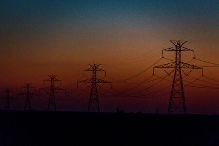 Scenery of silhouetted electrical power lines and tower during sunset. Imagens