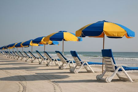 Beach chairs lined up in the sand awaiting sunbathers