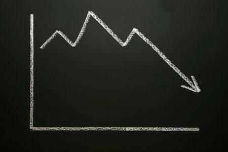 Business graph on blackboard showing a downward trend