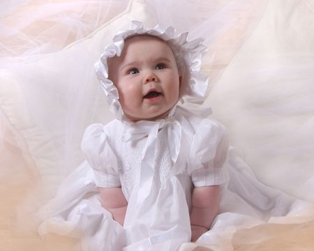 Smiling baby dressed in white with bonnet photo