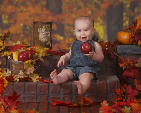 Adorable baby sitting on a brick stair eating an apple photo