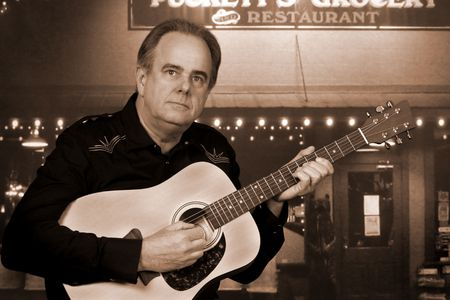 Country music singer performing outdoors in front of a rural restaurant Stock Photo